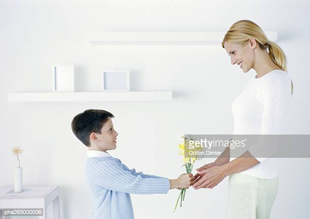 Boy holding out flowers to mother