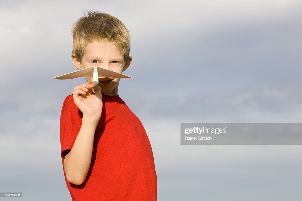 Boy (10-12) holding paper plane : Stock Photo