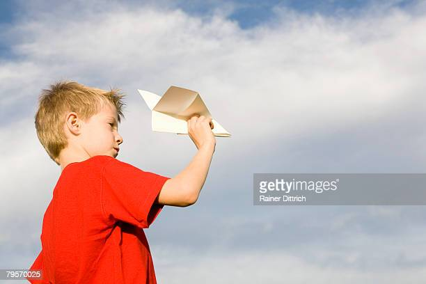'Boy (10-12) holding paper plane, side view'
