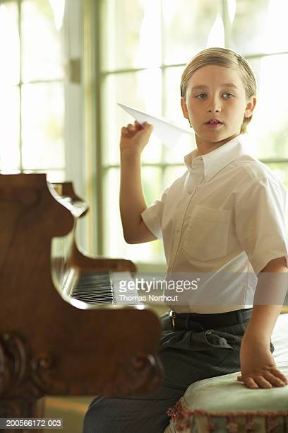 Boy (8-10) holding paper plane sitting at piano