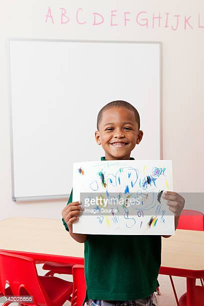 Boy holding picture that he has drawn in school