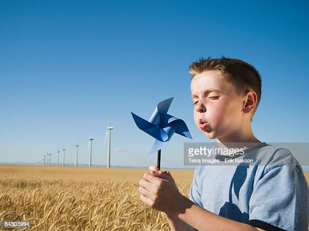Boy holding pinwheel on wind farm
