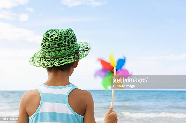 Boy holding pinwheel, watching sea, rear view