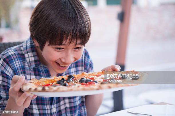 Boy holding pizza