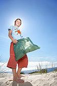Boy (10-12) holding plastic bag, on sand dune, portrait