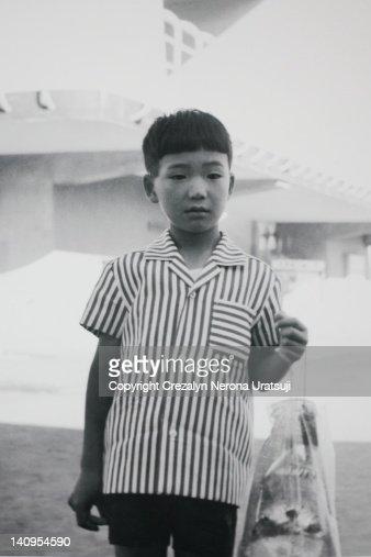 Boy holding plastic bag with goldfish and stone : Stock Photo