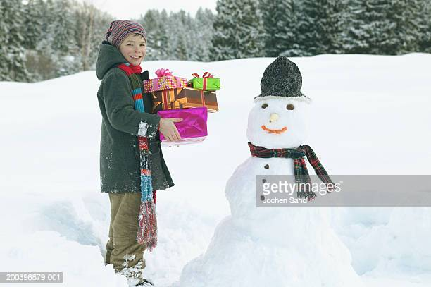 Boy (8-10) holding presents by snowman, smiling, portrait