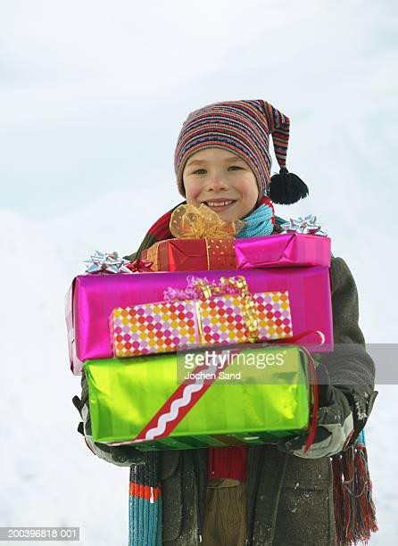 Boy (8-10) holding presents in snow, smiling, portrait, close-up