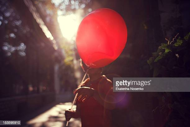 Boy holding red ballon