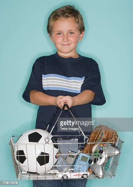 Boy holding shopping basket with toys