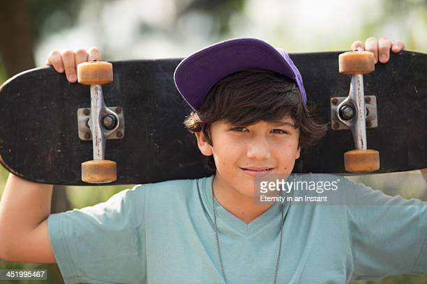 Boy holding skateboard behind his head.