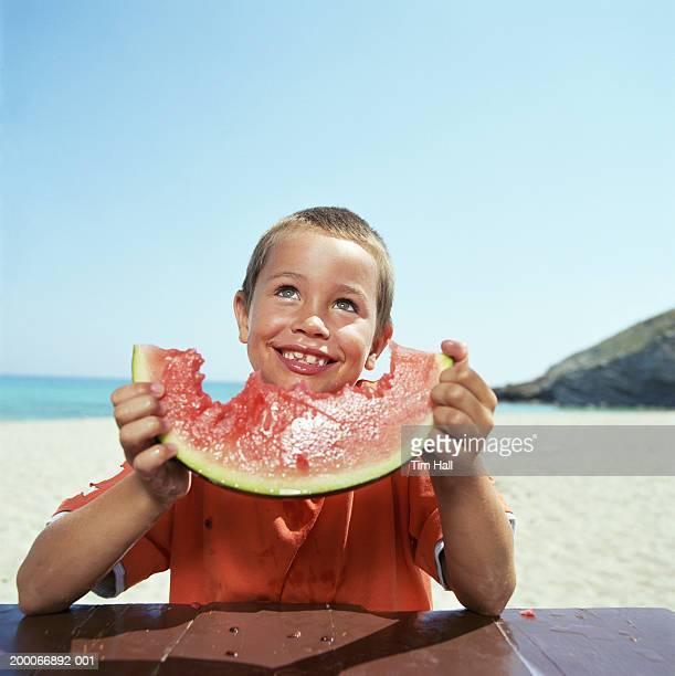 Boy (6-8) holding slice on watermelon on beach, smiling
