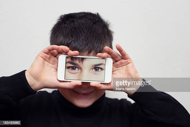 Boy holding smartphone over eyes