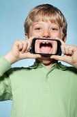 Boy holding smartphone over mouth