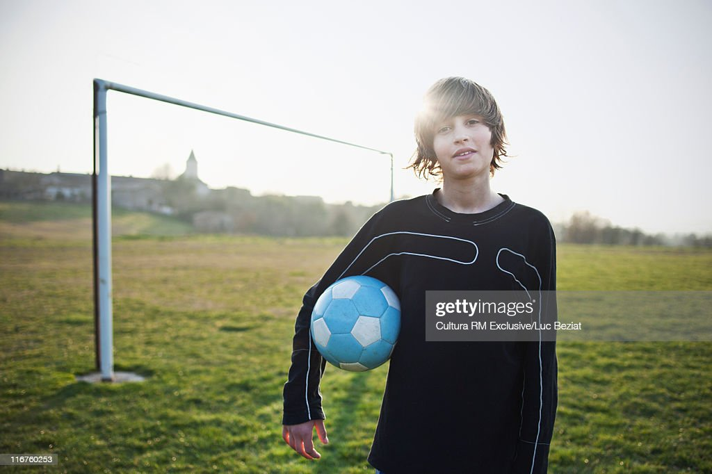 Boy holding soccer ball outdoors : Stock Photo