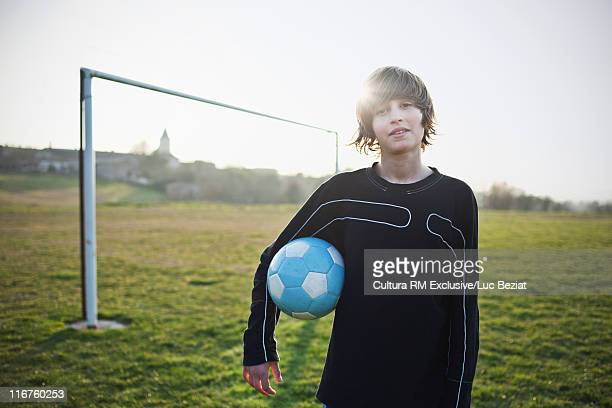 Boy holding soccer ball outdoors
