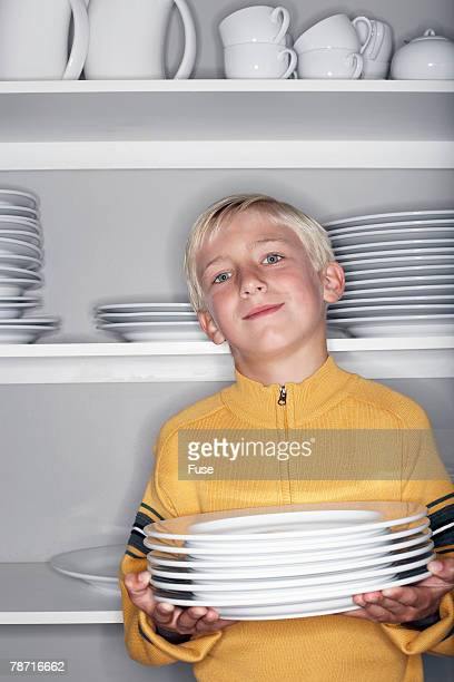 Boy Holding Stack of Plates