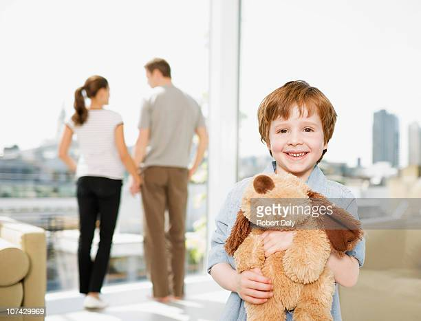 Boy holding stuffed dog with parents in background