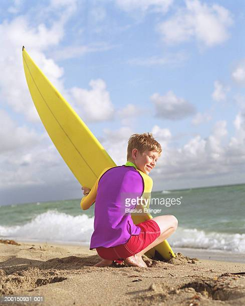 Boy (8-10) holding surfboard on beach