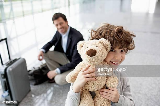 Boy (5-6) holding teddy bear, father in background