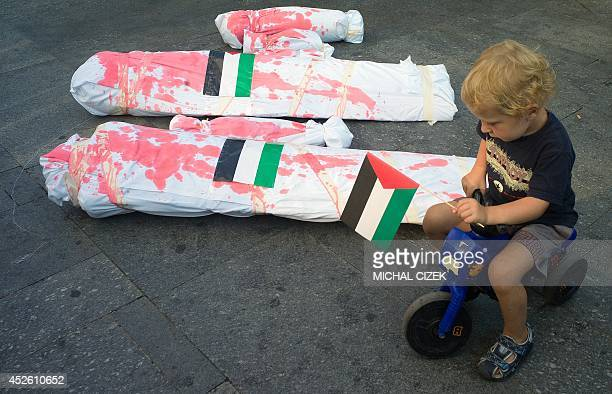 A boy holding the Palestinian flag rides on his plastic motorbike around mockups of dead Gaza children during a rally in solidarity with Palestinians...