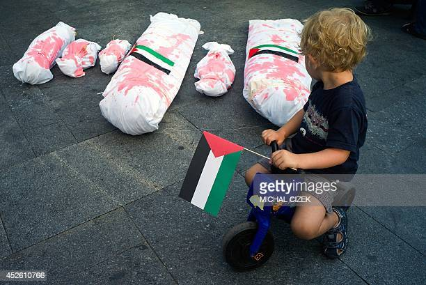A boy holding the Palestinian flag rides on his plastic motorbike around mockups of dead Gaza residents during a rally in solidarity with...