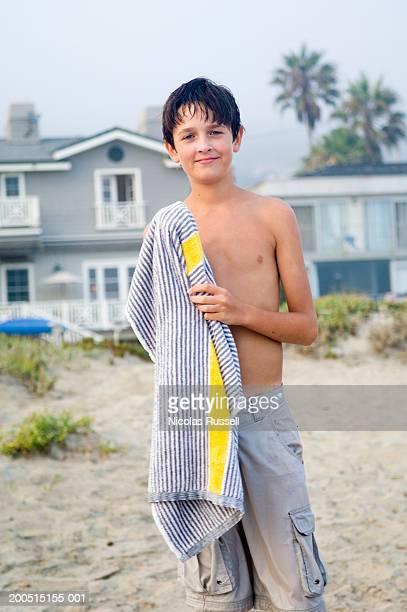 Boy (11-13) holding towel on beach, portrait