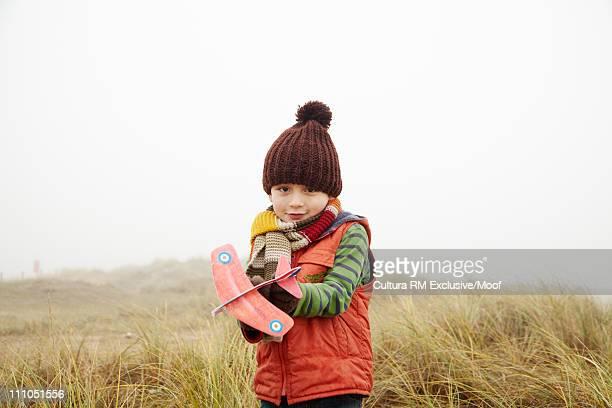 Boy holding toy aeroplane in foggy field