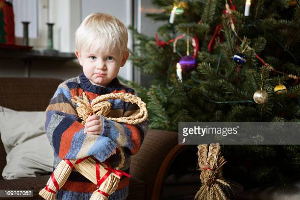 Boy holding toy by Christmas tree