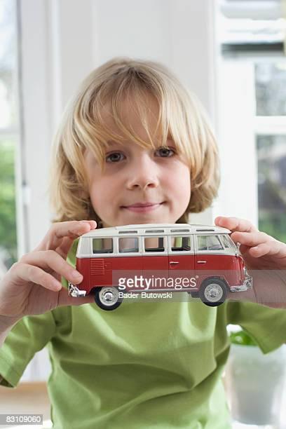 Boy (6-7) holding toy bus, portrait, close-up