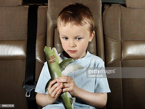 Boy holding toy in car