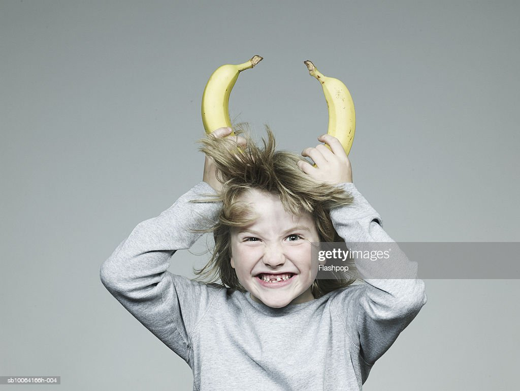Boy (6-7) holding two banana on head, smiling, close-up