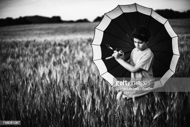 Boy Holding Umbrella At Wheat Field