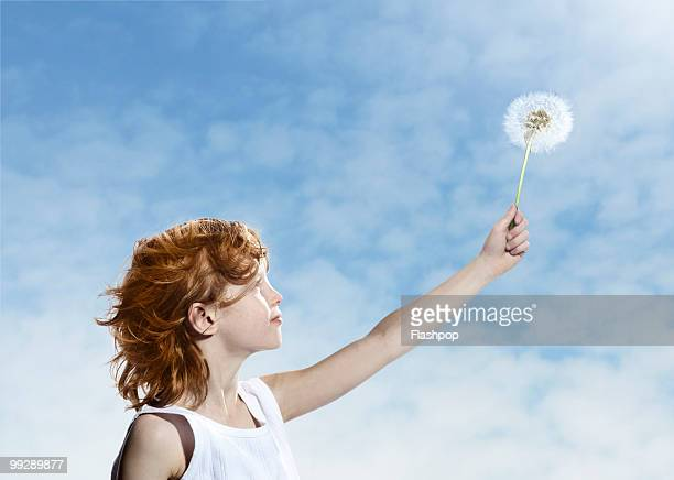 Boy holding up a dandelion to the sky