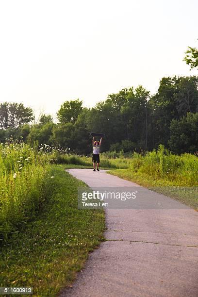 Boy holding up a skateboard