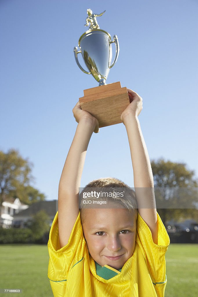 A boy holding up a trophy : Stock Photo