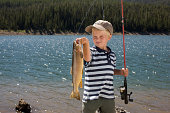 Boy looking a fish he just caught by lakeside