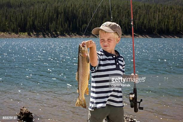 Garçon tenant un poisson Il a attrapé