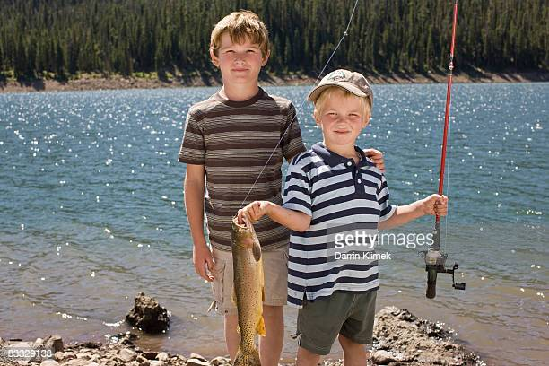 Boy holding up fish he caught