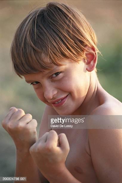 Boy (8-9) holding up fist, smiling, portrait