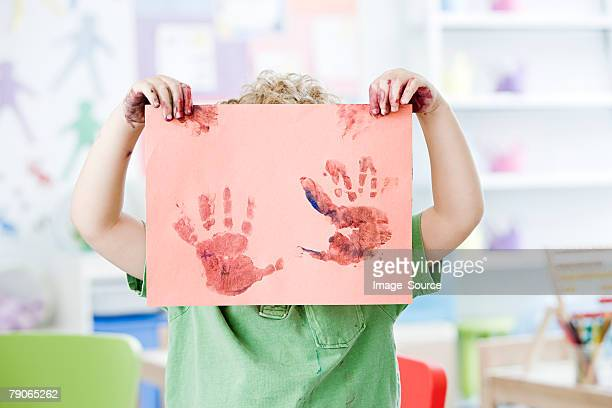 Boy holding up painted hand print