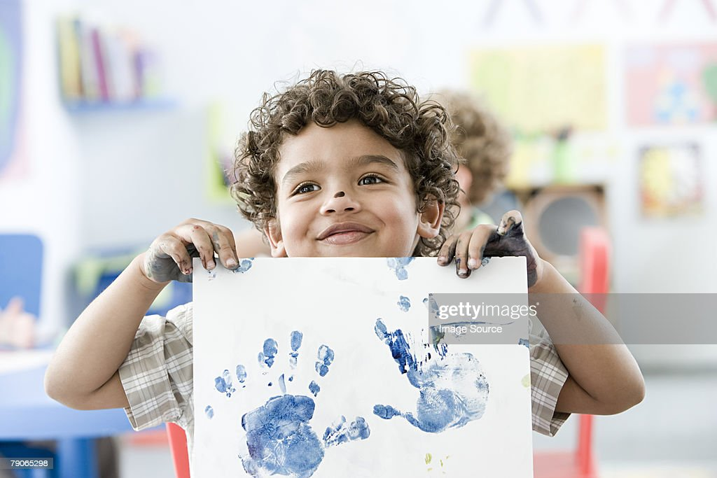 Boy holding up painted hand print : Stock Photo