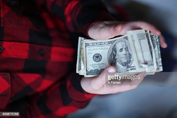 Boy holding wad of US Dollars
