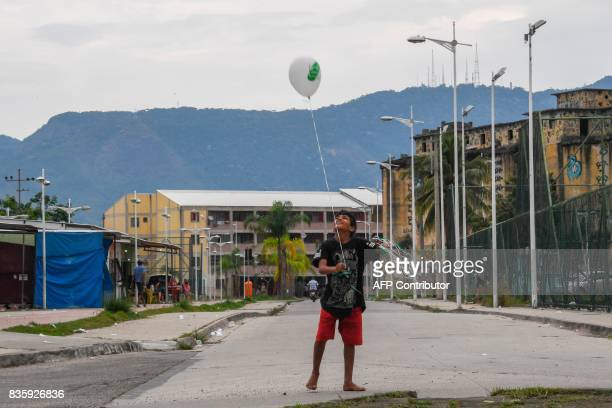 A boy holds a balloon as residents of Rio de Janeiro's Jacarezinho and Manguinhos favelas march in demand of peace in Rio Brazil on August 20 2017 In...