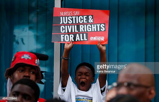 A boy holds a banner during rally against police violence on August 23 2014 in the borough of Staten Island in New York City Thousands of marchers...