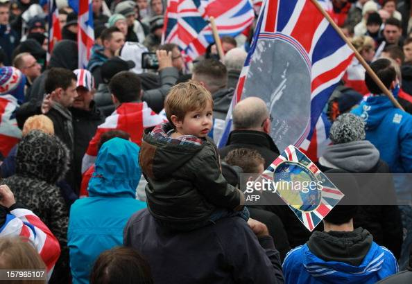 A boy holds a British Union Flag with a picture of Queen Elizabeth II during a loyalist protest outside the city hall in Belfast Northern Ireland on...