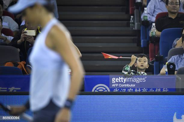 A boy holds a Chinese flag as he watches the women's singles final match between Caroline Garcia of France and Ashleigh Barty of Australia at the WTA...