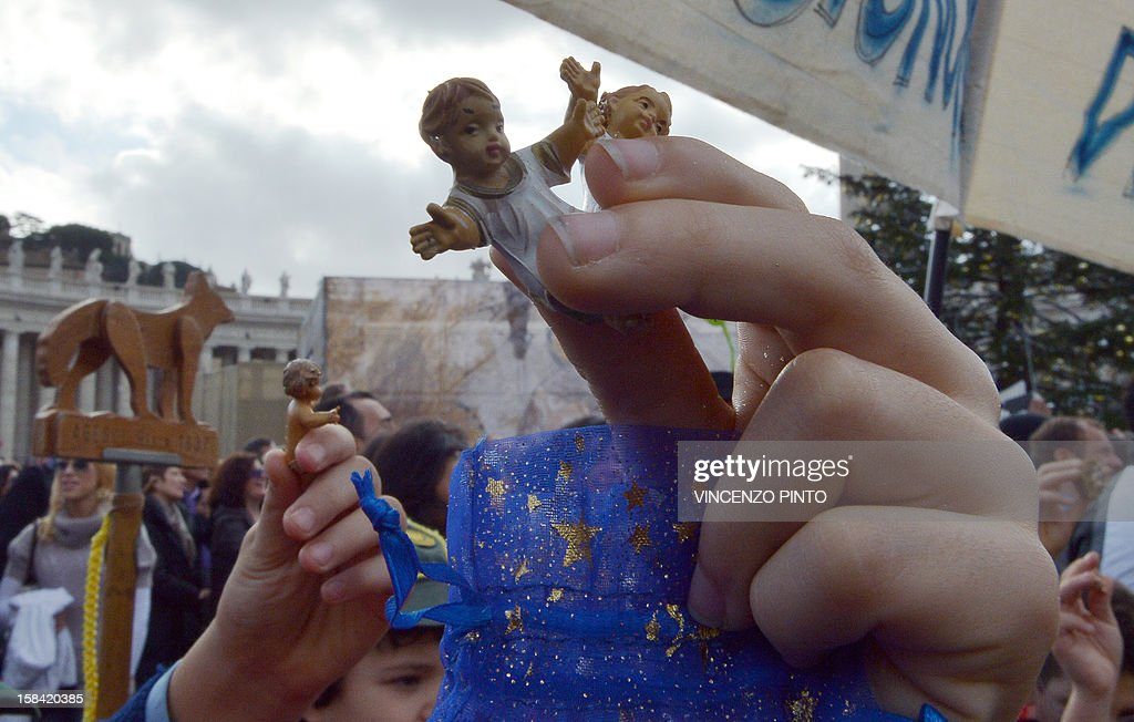 A boy holds a effigy of the infant Jesus to be blessed by Pope Benedict XVI during his weekly Angelus prayer on December 16, 2012 at the Vatican. The pontiff prayed for families of the victims in the Newtown, Connecticut, school massacre in the United States during his traditional weekly address to pilgrims on St Peter's Square. AFP PHOTO / VINCENZO PINTO