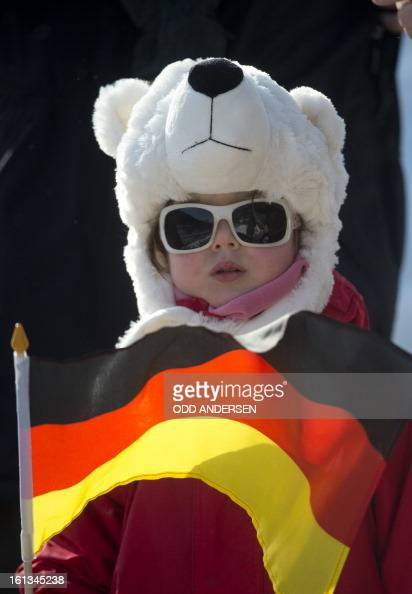 A boy holds a German flag as the start of the FIS Ski Jumping World Cup individual large hill competition has been delayed on the Muehlenkopfschanze...