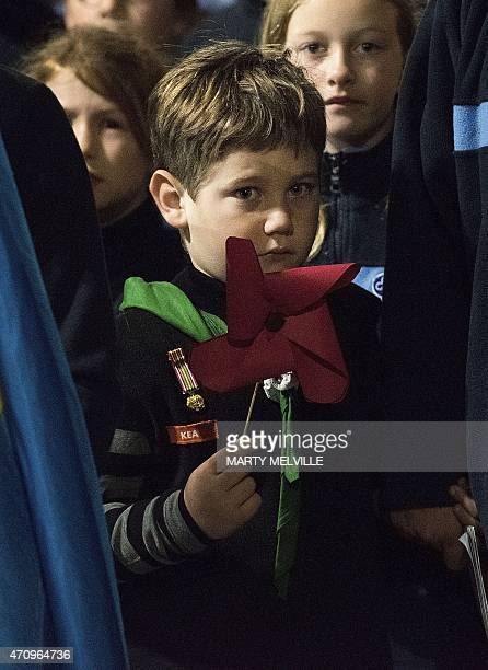 A boy holds a large poppy during ANZAC day commemorations at Pukeahu National War Memorial Park in Wellington New Zealand on April 25 2015 Ceremonies...